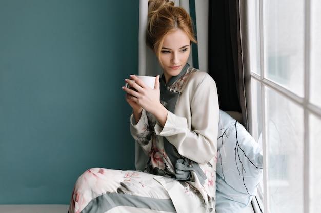 Porträt der schönen jungen frau mit sinnlichem blick durch fenster, sitzend auf fensterbrett mit tasse kaffee in ihren händen. türkisfarbene wand. gekleidet in seidenpyjamas mit blumen.