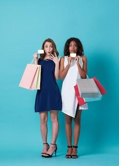 Porträt der schönen jungen frau zwei, welche die kreditkarte und einkaufstasche lokalisiert über blauem hintergrund zeigt.
