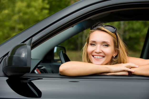 Porträt der schönen jungen fröhlichen frau im neuen auto - im freien