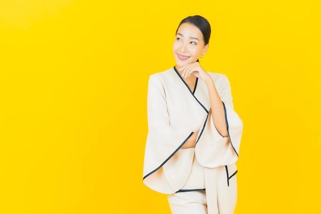 Porträt der schönen jungen geschäftsasiatin, die mit weißem anzug auf gelber wand lächelt