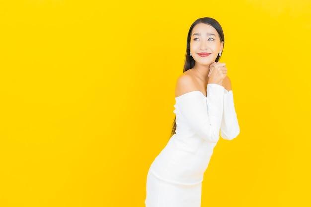 Porträt der schönen jungen geschäftsasiatin, die mit weißem kleid auf gelber wand lächelt