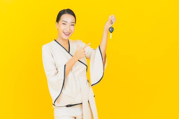 Porträt der schönen jungen geschäftsasiatin mit autoschlüssel auf gelber wand
