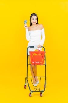 Porträt der schönen jungen geschäftsasiatin mit einkaufskorb mit lebensmittelgeschäft vom supermarkt auf gelber wand