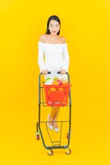 Porträt der schönen jungen geschäftsasiatin mit einkaufskorb mit lebensmitteln vom supermarkt auf gelber wand