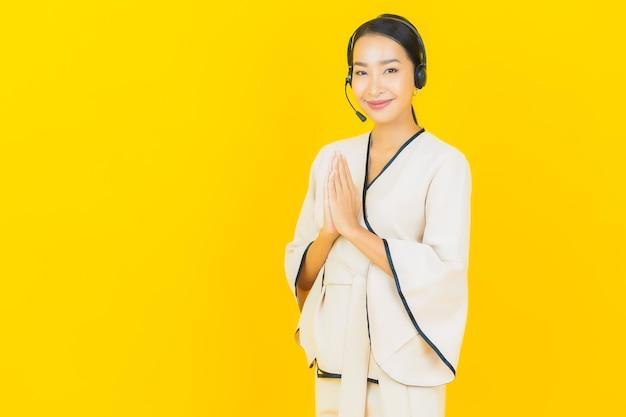 Porträt der schönen jungen geschäftsasiatin mit headset für callcenter-kundenbetreuung auf gelber wand