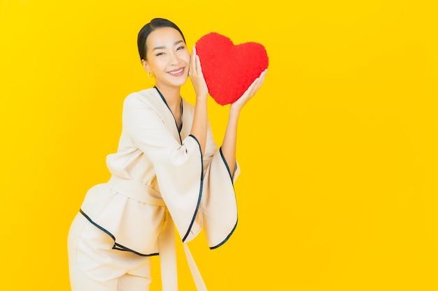 Porträt der schönen jungen geschäftsasiatin mit herzformkissen auf gelber farbwand