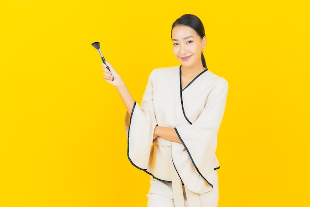 Porträt der schönen jungen geschäftsasiatin mit make-up-kosmetikpinsel auf gelber wand