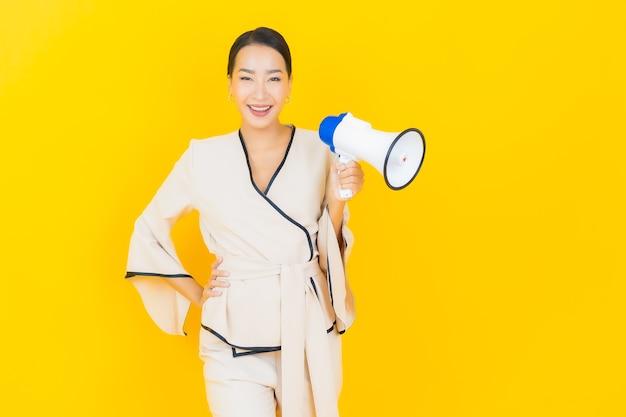 Porträt der schönen jungen geschäftsasiatin mit megaphon für kommunikation auf gelber wand