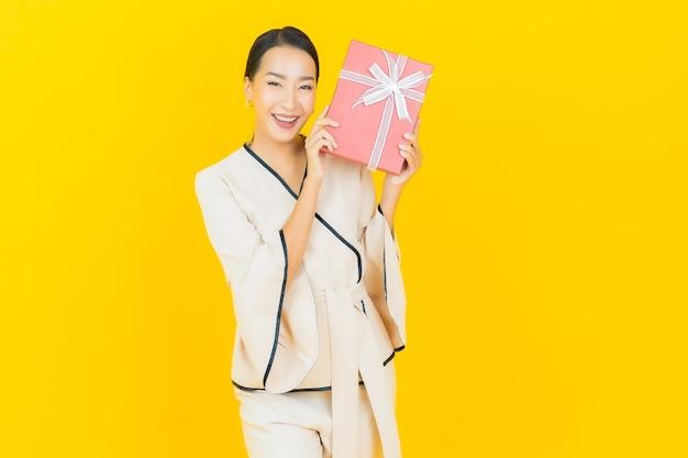 Porträt der schönen jungen geschäftsasiatin mit roter geschenkbox auf gelber wand