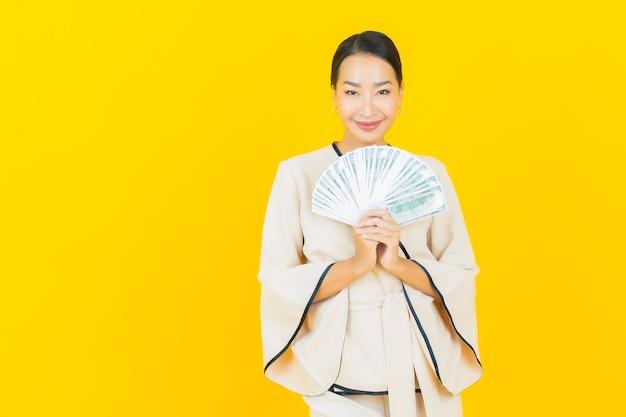Porträt der schönen jungen geschäftsasiatin mit viel bargeld und sparschwein auf gelber wand