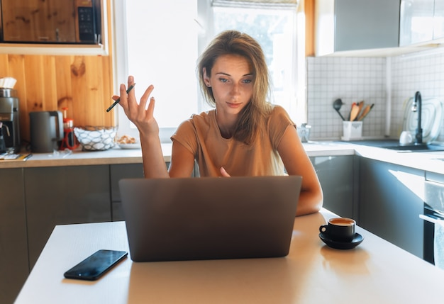 Porträt der schönen jungen geschäftsfrau, die am laptop im heimbüro arbeitet. freiberufliches fernarbeitskonzept