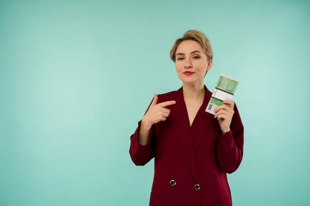 Porträt der schönen jungen geschäftsfrau, die finger auf geld zeigt, auf blauem hintergrund - bild