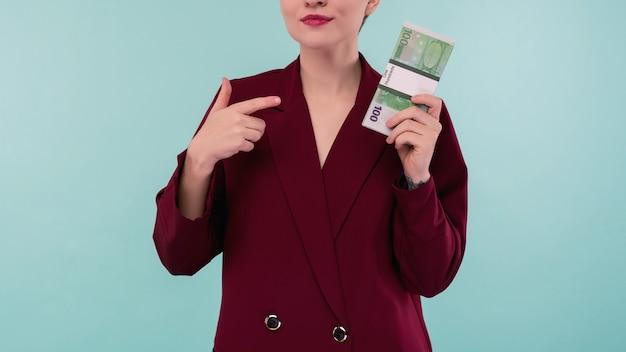 Porträt der schönen jungen geschäftsfrau, die finger auf geld zeigt, auf blauem hintergrund