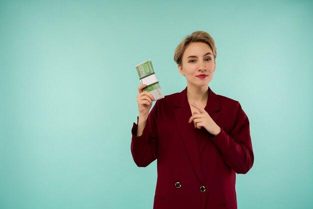 Porträt der schönen jungen geschäftsfrau, die finger auf geld zeigt
