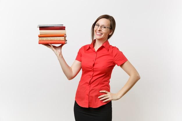 Porträt der schönen jungen geschäftslehrerfrau im roten hemd, im schwarzen rock und in den gläsern, die bücher in den händen lokalisiert auf weißem hintergrund halten. bildung oder lehre im hochschulkonzept