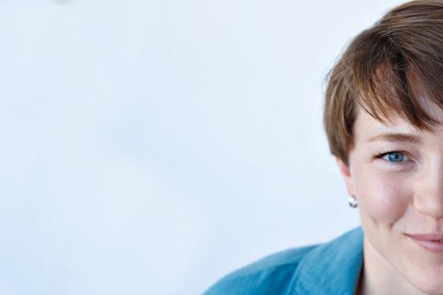 Porträt der schönen jungen glücklichen lächelnden frau mit den kurzen haaren in der blauen kleidung, halbes gesicht
