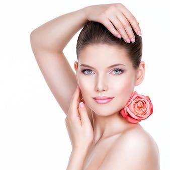 Porträt der schönen jungen hübschen frau mit gesunder haut und rosa rose nahe gesicht - lokalisiert auf weiß.