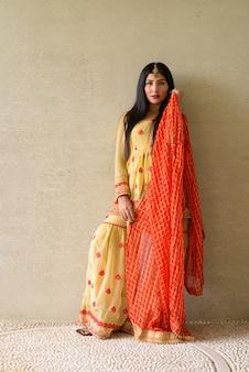 Porträt der schönen jungen indischen frau, die draußen traditionelle kleidung trägt