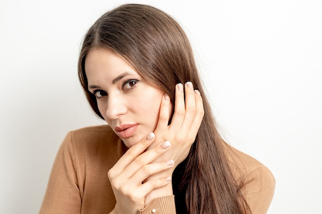 Porträt der schönen jungen kaukasischen brünetten frau mit dem berühren ihres haares durch gepflegte finger auf weißer wand