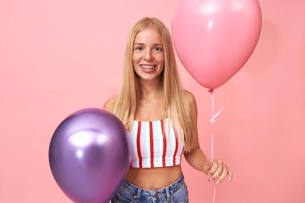 Porträt der schönen jungen kaukasischen frau mit dem glatten blonden haar und den hosenträgern, die stilvolles sommeroberteil tragen, das spaß hat, mit festlicher dekoration aufwirft und zwei heliumballons hält