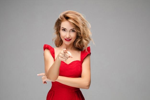 Porträt der schönen jungen kaukasischen frau mit langen blonden haaren, hellem make-up, roten lippen im roten kleid zeigt auf sie