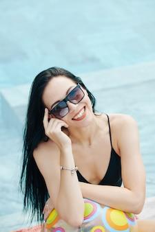 Porträt der schönen jungen lächelnden frau mit dem langen dunklen haar, das im schwimmbad mit aufblasbarem ball steht