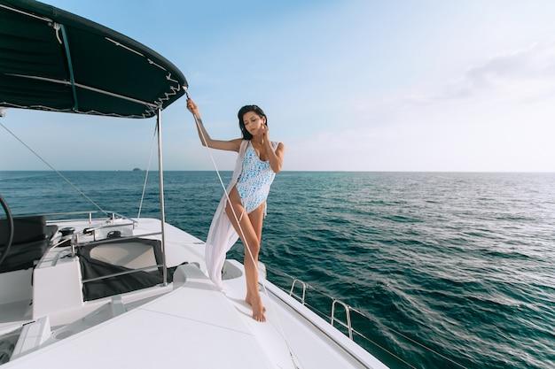 Porträt der schönen jungen modefrau, die auf segelboot oder yacht steht und aufwirft