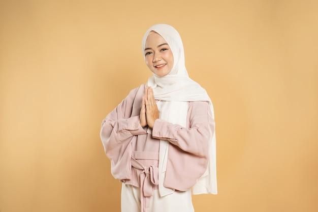 Porträt der schönen jungen muslimischen frau, die kamera betrachtet, die hand zusammen geste zeigt
