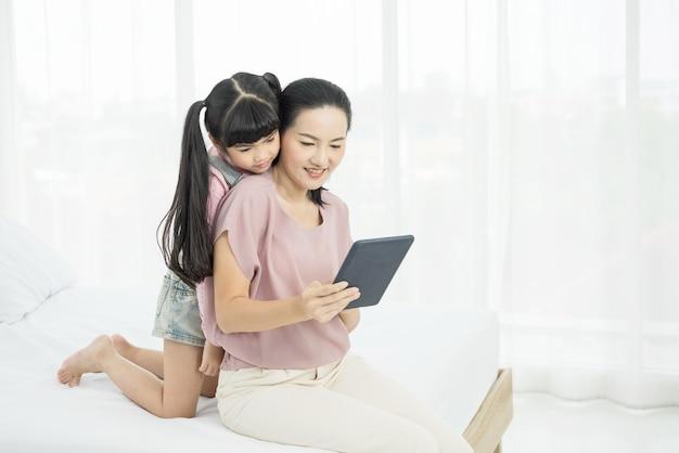 Porträt der schönen jungen mutter mit mädchen, das auf dem bett in einem moment der intimität sitzt, während produkte online mit tablette, sozialer distanzierung und online-bildungskonzept kauft.