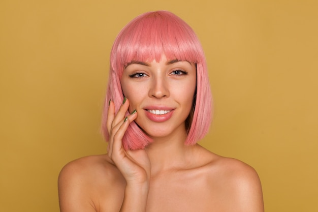 Porträt der schönen jungen positiven frau mit rosa bobfrisur, die mit ruhigem gesicht schaut und hand zu ihrer wange erhebt, über senfwand aufwirfend