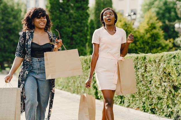 Porträt der schönen jungen schwarzen frauen mit einkaufstaschen