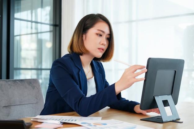 Porträt der schönen jungen unternehmergeschäftsfrau, die im modernen arbeitsplatz arbeitet.
