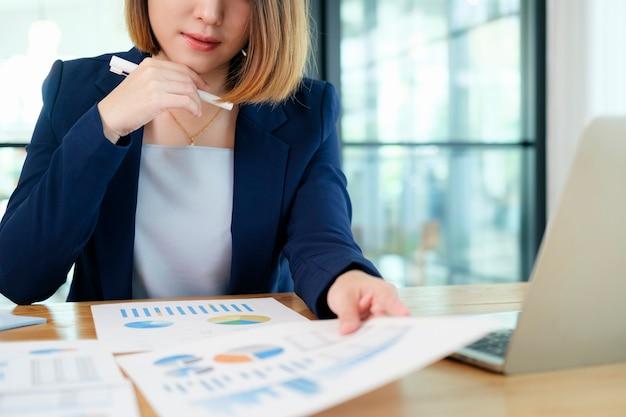 Porträt der schönen jungen unternehmergeschäftsfrau, die im modernen arbeitsplatz arbeitet. Premium Fotos
