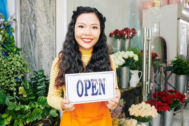 Porträt der schönen jungen vietnamesischen frau, die im blumenladen mit offenem zeichen steht