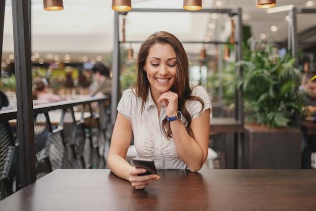 Porträt der schönen kaukasischen brünette, die im café sitzt und nachricht auf smartphone liest.