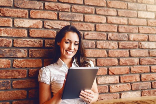 Porträt der schönen kaukasischen brünette mit zahnigem lächeln unter verwendung der tablette und des sitzens in der cafeteria. im hintergrund backsteinmauer.