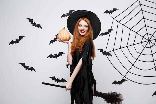 Porträt der schönen kaukasischen hexe, die kürbis zum feiern von halloween hält