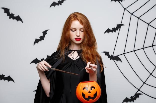 Porträt der schönen kaukasischen hexe, die orange kürbis zum feiern von halloween hält.