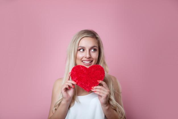 Porträt der schönen kaukasischen lächelnden frau mit rotem herzen auf rosa wand