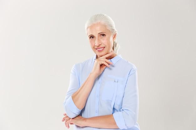 Porträt der schönen lächelnden älteren dame, die ihr kinn berührt
