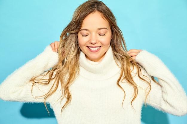 Porträt der schönen lächelnden blonden herrlichen frau. frau, die in der stilvollen weißen strickjacke, auf blauer wand steht. konzept des winters