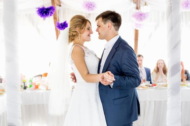 Porträt der schönen lächelnden braut und des bräutigams, die in der restauranthalle tanzen