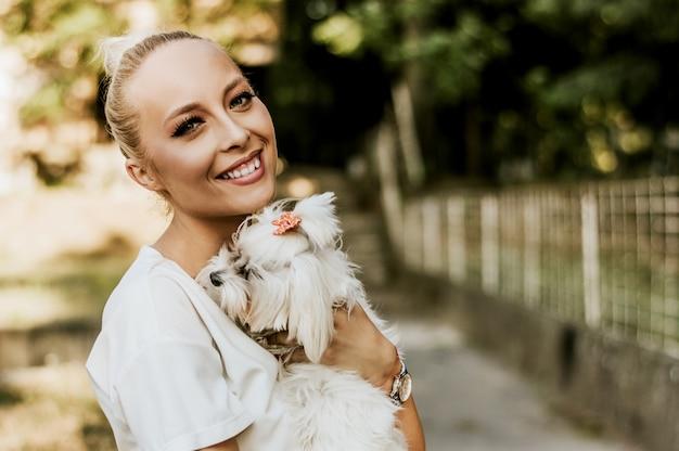 Porträt der schönen lächelnden frau, die maltesischen hund hält