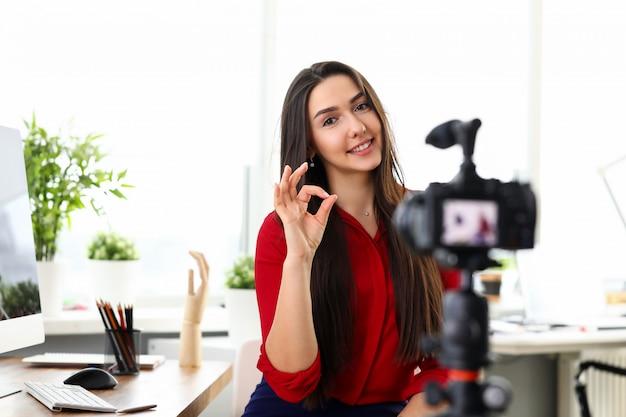 Porträt der schönen lächelnden frau, die video-blog auf videokamera aufzeichnet