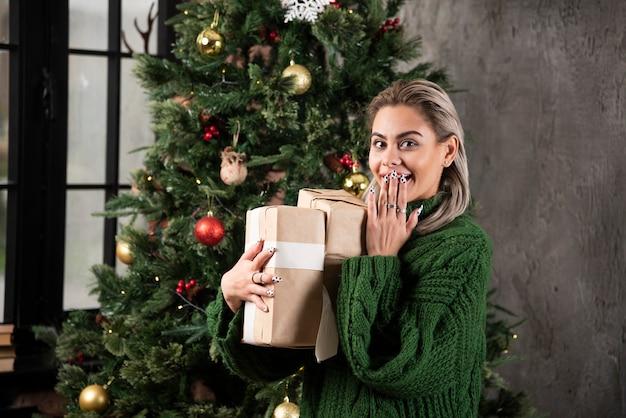 Porträt der schönen lächelnden frau im grünen pullover, der stapel von geschenkboxen hält