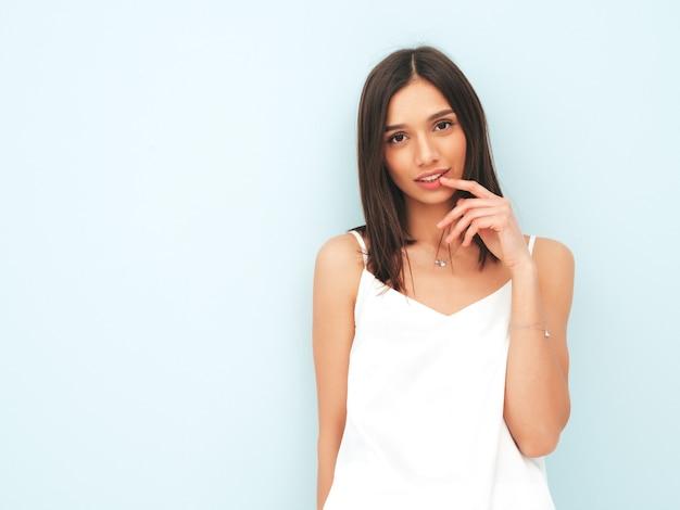 Porträt der schönen lächelnden frau im weißen pyjama gekleidet.
