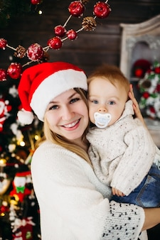Porträt der schönen lächelnden frau mit frisur und make-up, die ihr reizendes baby gegen geschmückten weihnachtsbaum halten