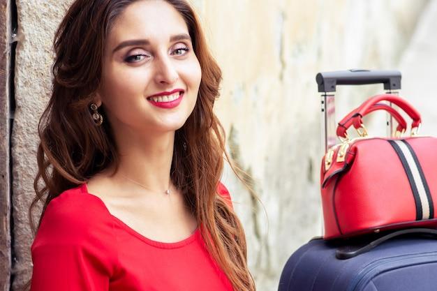 Porträt der schönen lächelnden frau mit koffer im roten kleid über alter mauer.