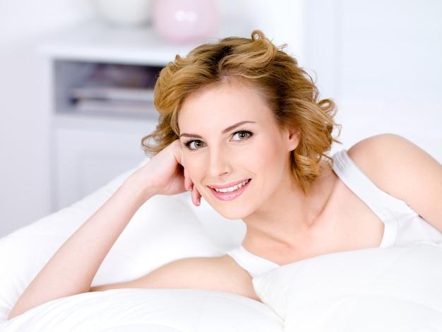 Porträt der schönen lächelnden hübschen frau entspannend - drinnen