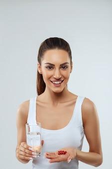 Porträt der schönen lächelnden jungen frau mit einer handvoll vitaminpillen. glückliches mädchen, das medikamente und glas frisches wasser in der hand hält.